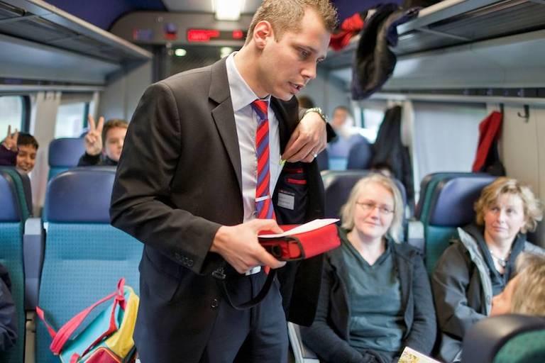 Контролёр проверят билеты в поезде.
